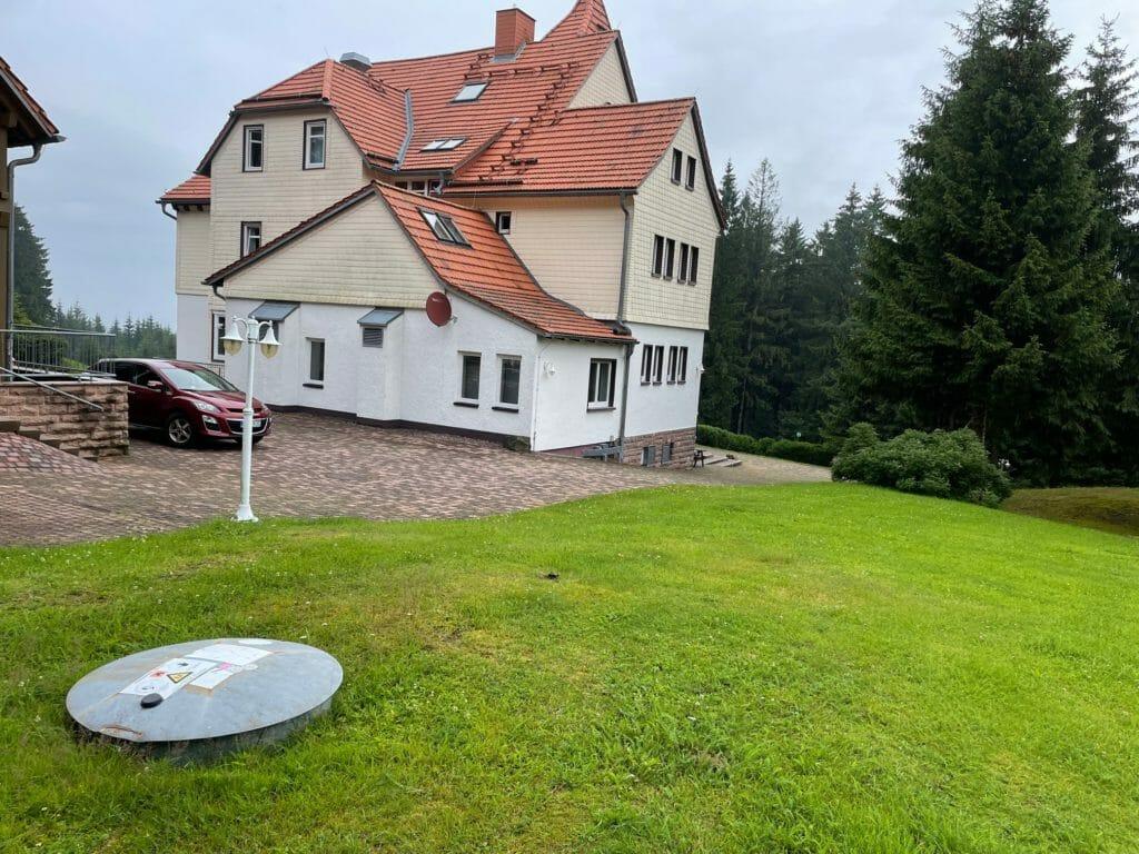 Domschachtdeckel eines unterirdischen Flüssiggastank auf einer Wiese vor Haus